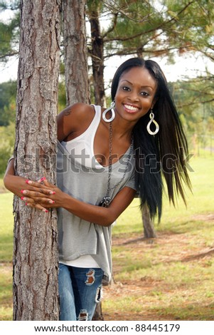 An extraordinarily beautiful young woman with a bright, warm smile leans against a pine tree outdoors.