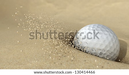 An extreme close up of a golf ball hitting the sand in a bunker and emitting grains of sand forwards