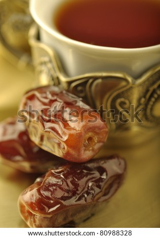 An extreme close up of arabic dates and tea cup