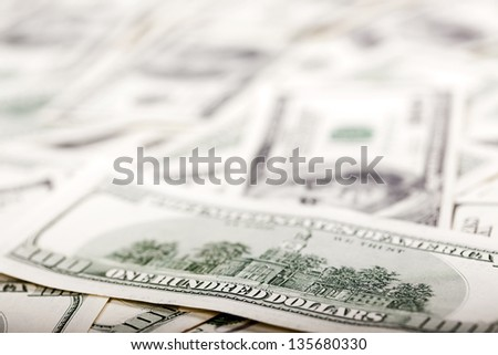 An extreme close up of the reverse side of a 100 US$ money note, with very shallow depth of field. Defocused in the background there's a very large amount of identical bills.