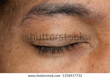 An extreme closeup view on the closed eyelids of an Asian man, eyesight and optical concept. #1358417732