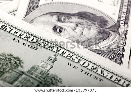 """An extreme macro shot of 100 US$ money notes, depicting the writing """"Untied States of America"""" and the portrait of Benjamin Franklin defocused in the background. Shallow depth of field."""