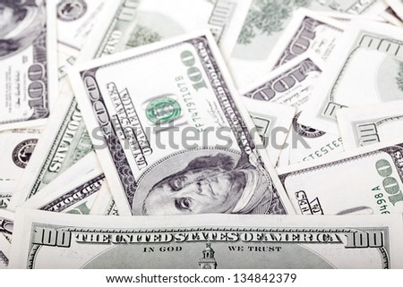 "An extreme macro shot of 100 US$ money notes, depicting the writing ""Untied States of America"" and the portrait of Benjamin Franklin, amongst the mess of many identical bills."