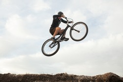 An extreme man jumping on the trial bicycle in the mountains. Horizontal outdoors shot.