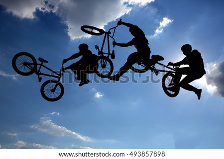 Photo of An extreme rider is making a free style jump from a ramp. The young boy with his bicycle is seen as a silhouette in front of the sun. Multiple exposure image. Clouds.