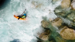 An extreme whitewater Kayaker paddling on the Emerald waters of Soca river, Slovenia, are the rafting paradise for adrenaline seekers and also nature lovers, aerial view.