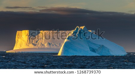 An extremely surreal looking pair of icebergs catching the last rays of sunlight in the Weddell sea, near het Antarctic Peninsula, just before sunset. #1268739370
