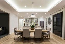 An eye-catching view of contemporary dining area attached to a modular kitchen having a 6-seater dining table with a bright pendant light hanging above it.