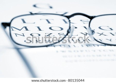 An eye chart with a pair of glasses and selective focus within the frames to emphasize vision correction.