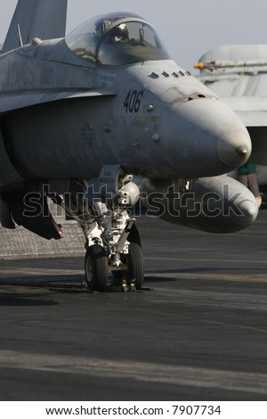 An F/A-18C Hornet Awaits a Catapult Assisted Launch Aboard a Nuclear Aircraft Carrier - stock photo