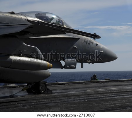 An F-18 Hornet sits moment before being catapulted off the deck of an aircraft carrier - stock photo