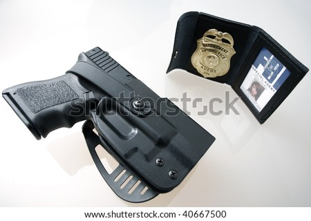 An FBI badge and pistol on a table.