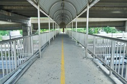 An footbridge with arched roofs, stainless steel stair rails and concrete steps that has shadow, The woman crossing the street on the overpass on faraway, close up.