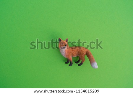 An fox animal is a children's toy. Plastic figurine for the game. Green background. Farm and the zoo.