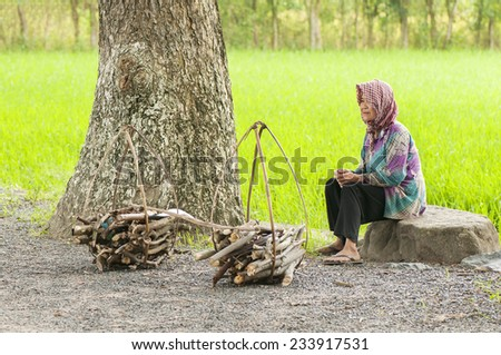 AN GIANG, VIETNAM - SEP 21, 2014: Khmer woman sitting on the road to rest for cribs. They sell cribs around market at An Giang, Vietnam.