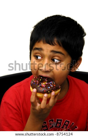 An handsome indian boy eating a chocolate dounut