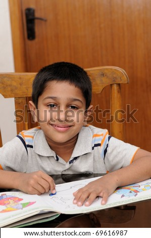 An handsome Indian kid doing his homework very happily