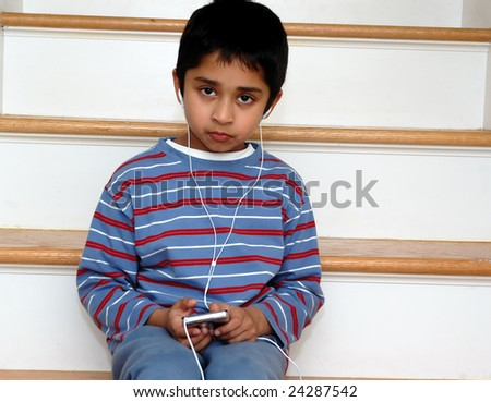 An handsome indian kid listening to music