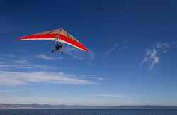 an hang glider flying over Bracciano lake, near Rome, italy in a very clear, sunny day
