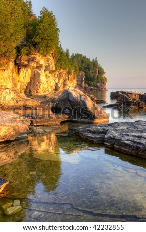 An HDR photo the golden morning light shinning on the rocky shorline of the Bruce Peninsula, in Ontario, Canada.