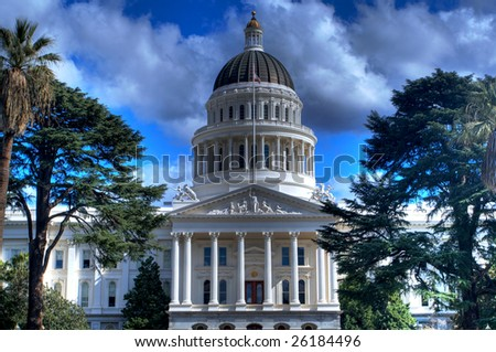 an  high dynamic range image of the California State Capital Building from a distance bordered by trees and a blue sky with Gray and white clouds