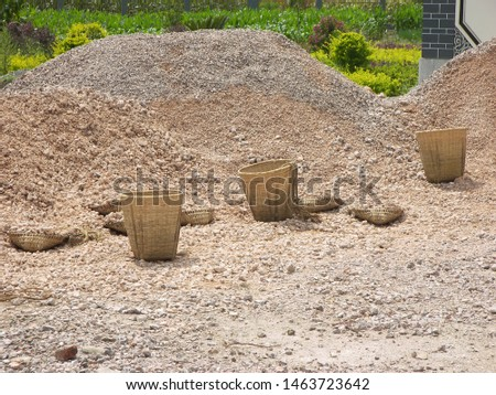 An hill of stones is in the country. The stones are carried using some baskets. Some green plants aer on the background. The photo has been taken in China.