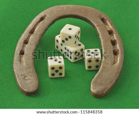 An horseshoe over green background with five dice