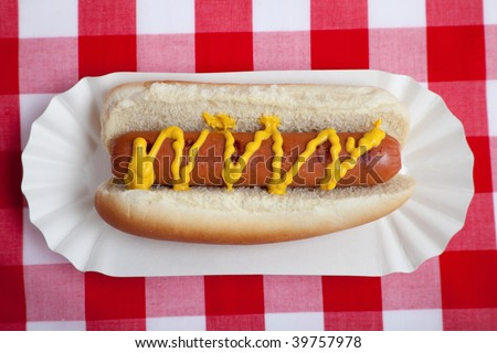 An hot dog with mustard on a red gingham background