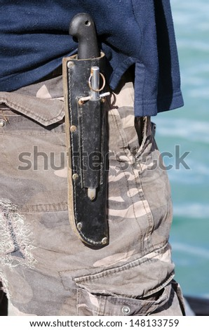 An hunting survival knife carry by a man on his belt outdoor.