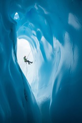 An ice climber in a green jacket and orange helmet rappels past a large rounded entrance to an ice cave on the Matanuska Glacier in Alaska.