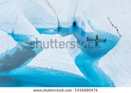An ice climbing guide floats an inflatable canoe on a deep blue lake on the glacier. The narrow flooded canyons leave fins of white ice that look like icebergs, but are still attached to the glacier. #1436880476