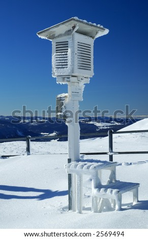 An ice-covered Stevenson Screen weather station, high on a mountain-top in Switzerland