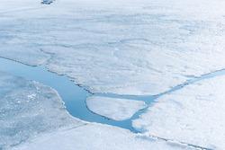 An ice floe breaks ups in the spring thaw revealing the frigid water below.