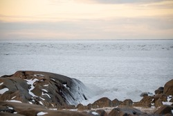 An icy and ice covered Hudson Bay in northern Canada, Churchill Manitoba with snow covered rocks on the beach shoreline.