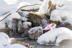 An icy and snowy stream. The snow and ice are melting in the springtime in Vermont. The water has formed icicles off the green and yellow rocks. The water is flowing slowly along the snow bank.