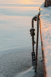 An icy rope at a jetty in the winter at a frozen lake in the sunset
