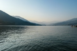 An idyllic view on Phewa Lake in Pokhara, Nepal. There are high Himalayan ranges around the lake. Calm surface of the lake. Clear and sunny day. There is a dence forest at the shore. Golden hour haze