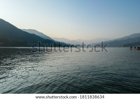 Photo of  An idyllic view on Phewa Lake in Pokhara, Nepal. There are high Himalayan ranges around the lake. Calm surface of the lake. Clear and sunny day. There is a dence forest at the shore. Golden hour haze