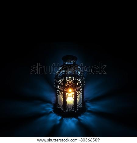 An illuminated Arabic lantern on back background - stock photo