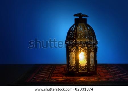 An illuminated Arabic lantern on blue background