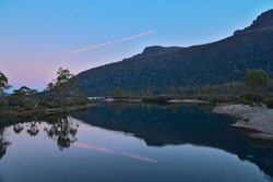 An illuminated magenta contrail and a mountain shadow reflecting on Lake Saint Clair at dusk. The Overland Track, Tasmania, Australia