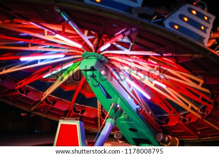 An illuminated rotating circular device in an amusement park. #1178008795