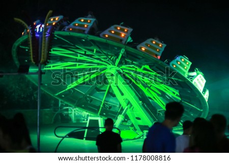 An illuminated rotating circular device in an amusement park. #1178008816