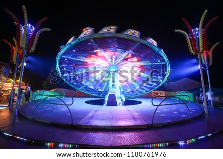 An illuminated rotating circular device in an amusement park. #1180761976