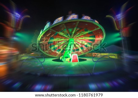 An illuminated rotating circular device in an amusement park with zoom in effect. #1180761979