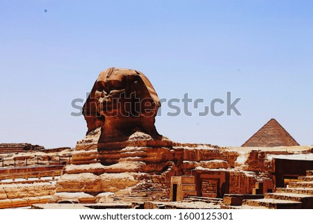 An illustration in a digital painting style of the great Sphynx of Giza in Egypt with a pyramid in the background. Digital artwork