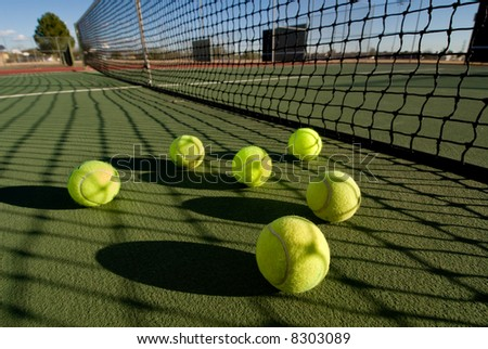 An image depicting the concept of tennis, including the court and balls at sunset.