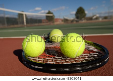 An image depicting the concept of tennis, including the court, racquets, balls and blue outdoors.