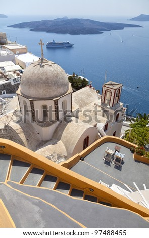 An image from the santorini capital town of fira with landmark church in the foreground.