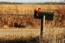 An image of a an old rural mailbox on a wooden post.